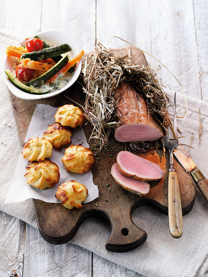 Mangalitza pork fillet wrapped in hay served with potato and parsnip fritters