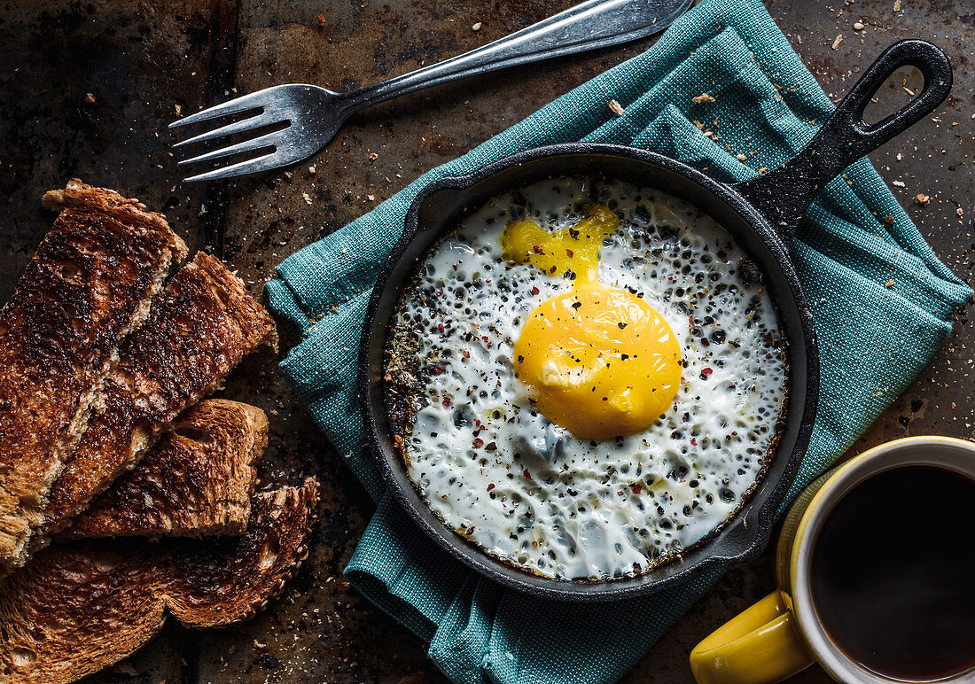 A fried egg in a pan, served with toast and coffee