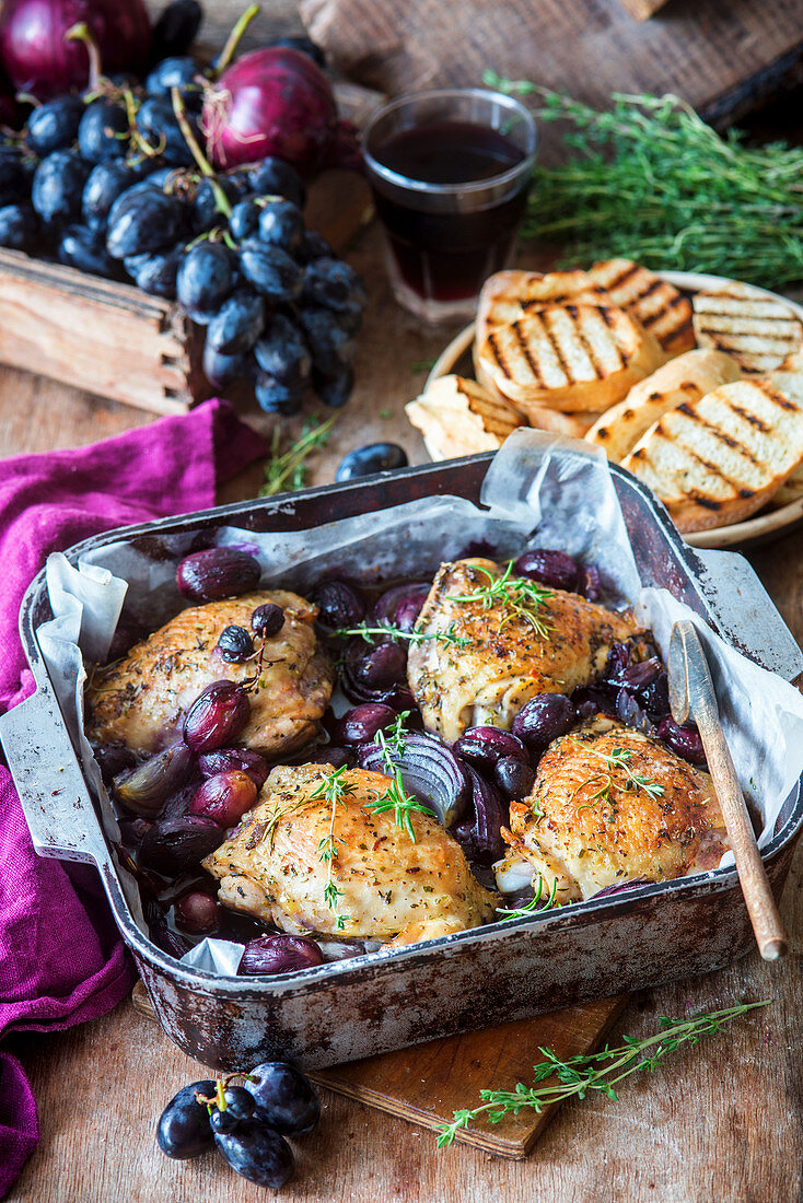 Roasted chicken thighs with grapes and thyme in a roasting pan