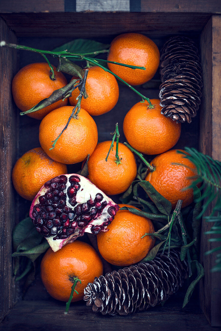 Mandarins and pomegranates in a wooden crate