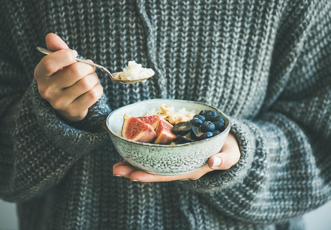 Healthy winter breakfast: Woman in woolen sweater eating rice coconut porridge with figs, berries, hazelnuts