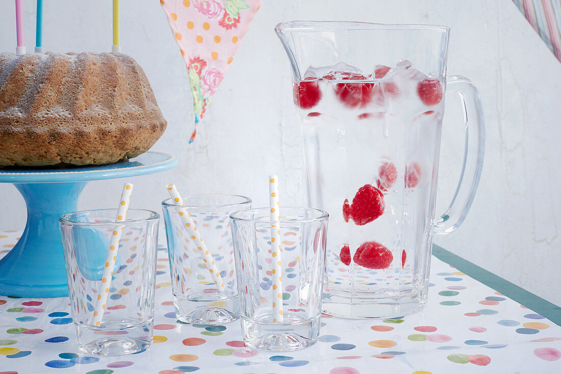 A jug with ice cubes on a table laid for a birthday party