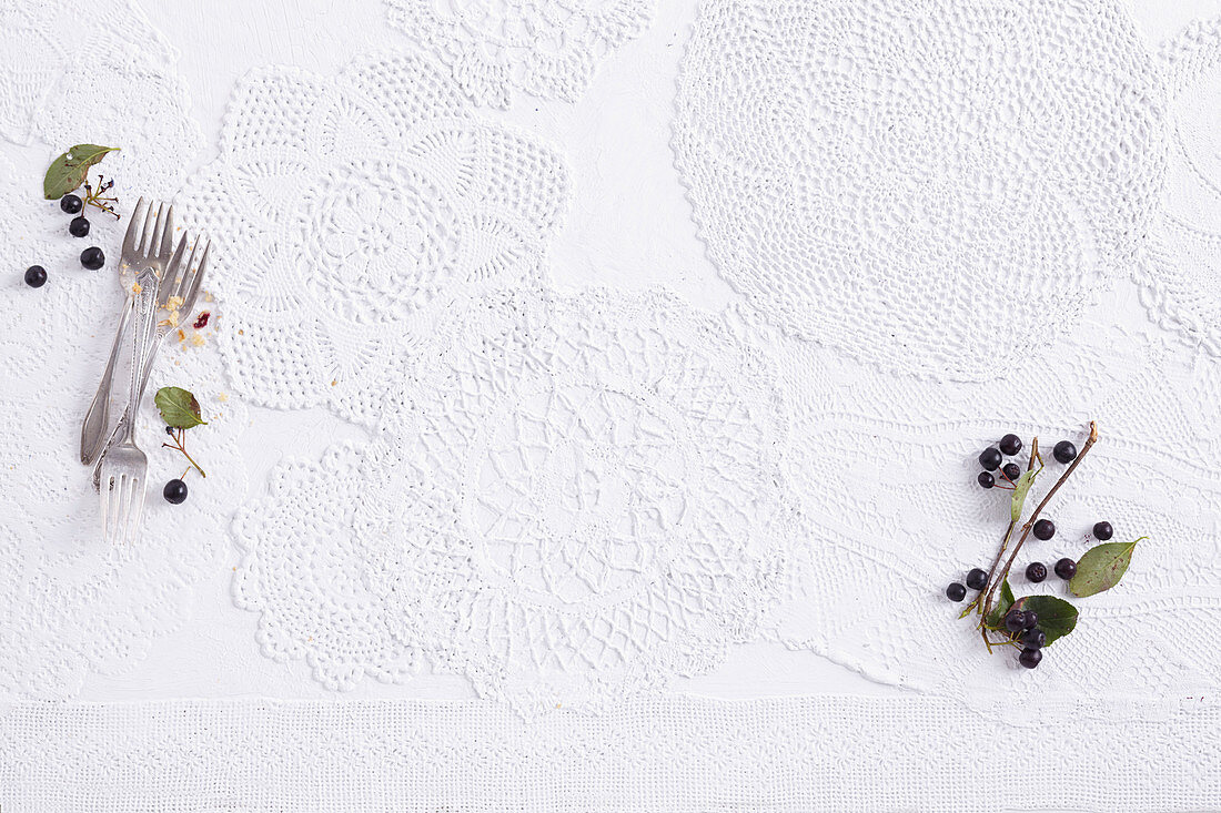 White doilies, cake forks and aronia berries
