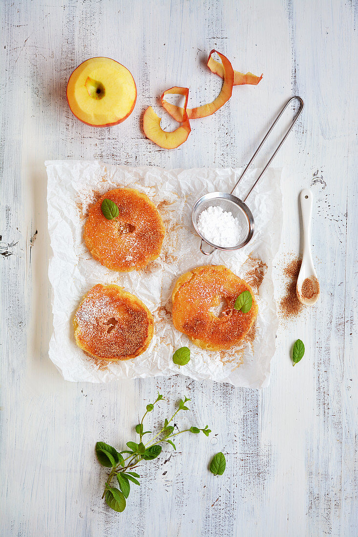 Battered apple rings with icing sugar, cinnamon and mint on a piece of paper