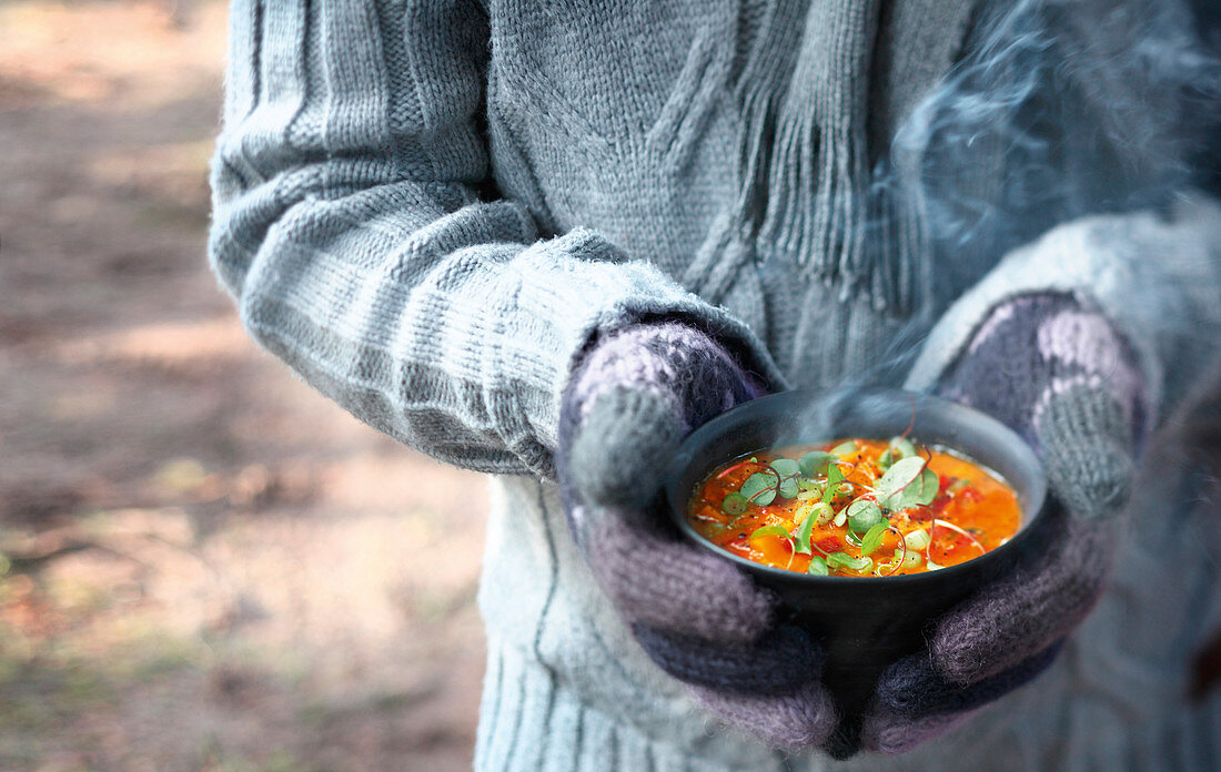 Gloved hands holding a bowl of warm soup from the grill