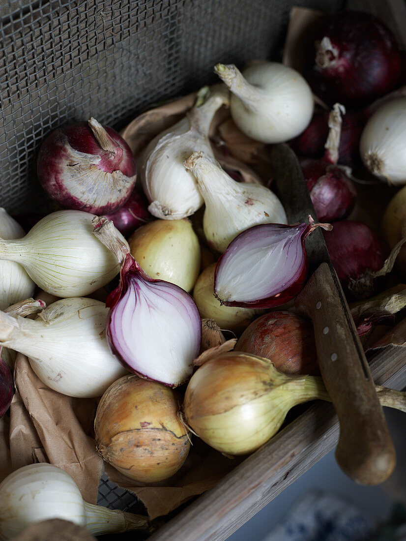 Various onions, whole and sliced, in a crate