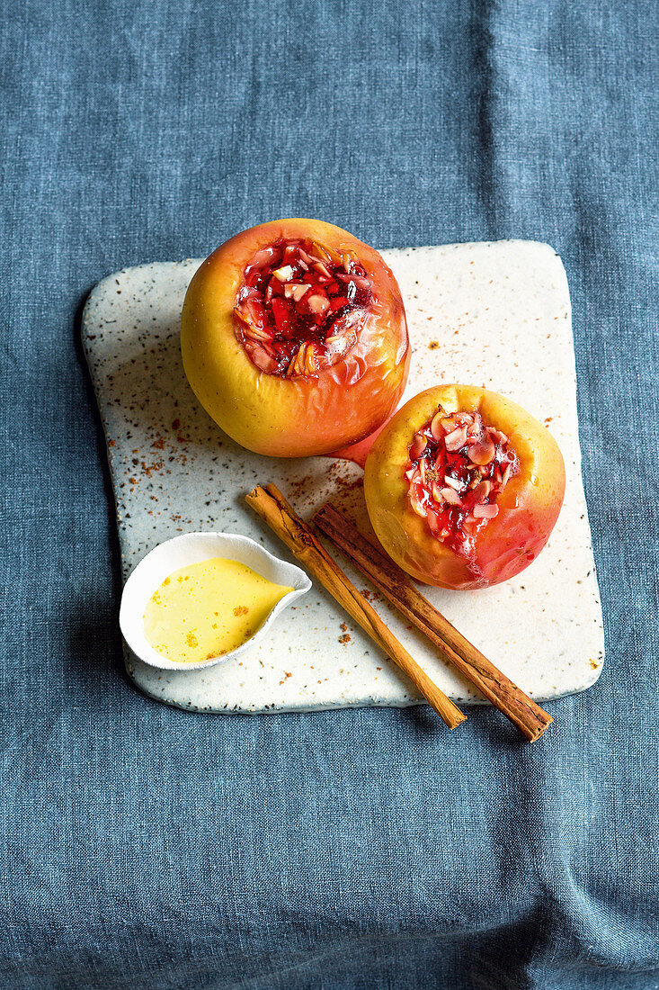 A baked apple with almonds and berry jam