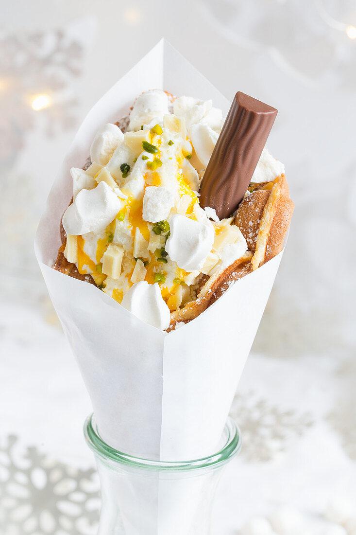A bubble waffle with frozen yoghurt, pistachios, meringue, chocolate flake and mango sauce (Christmas)