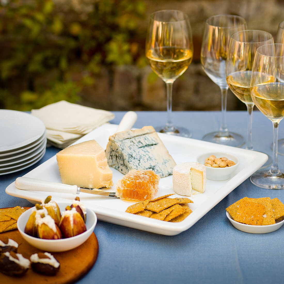Cheese platter with honey, crackers and figs