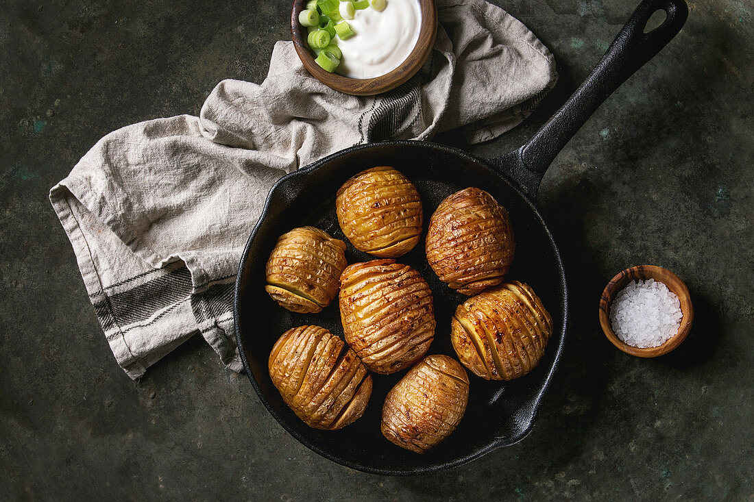 Accordion hasselback baked potatoes served in cast-iron pan with sea salt, cream-fresh and green spring onion on textile napkin