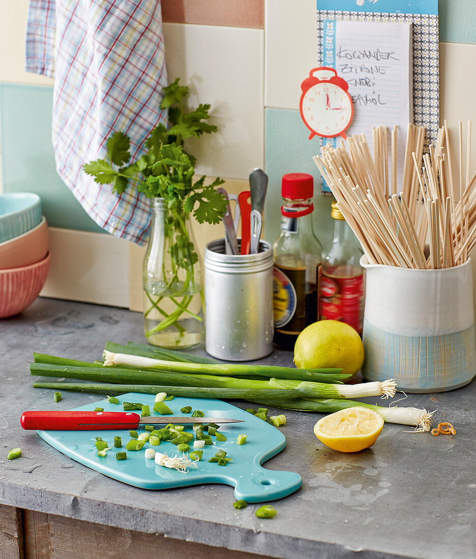 A kitchen scene – spring onions being sliced