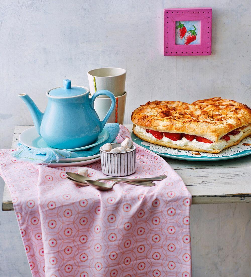 Tea crockery and a heart-shaped strawberry cake