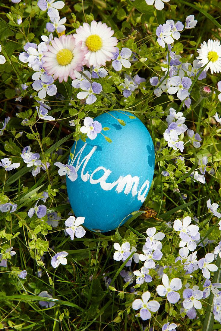 Blaues Ei mit Tafelfarbe bemalt und mit Schriftzug 'Mama' auf Frühlingswiese liegend