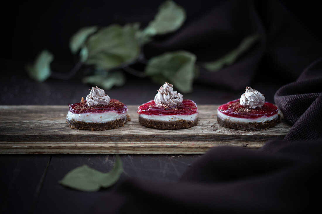 Vegan tartlets with a gingerbread base, quark cream, cherry jelly and a dollop of chocolate cream