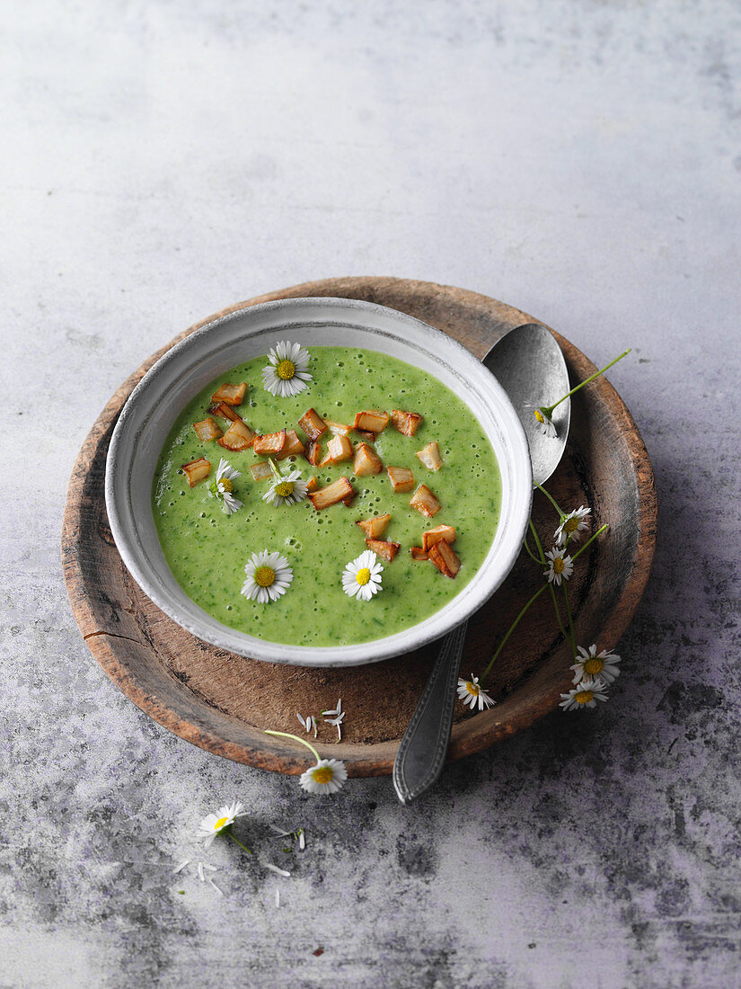 Vegan spring herb soup with daisies