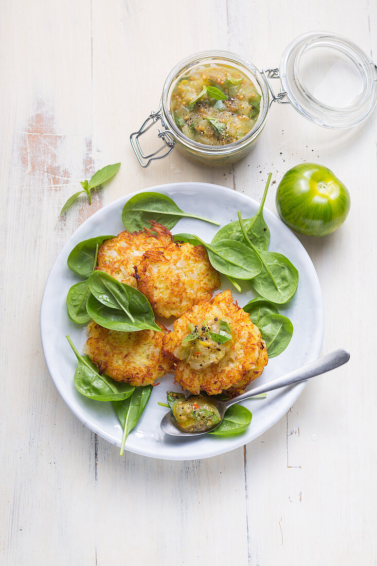 Potato fritters with green tomato chutney on baby spinach
