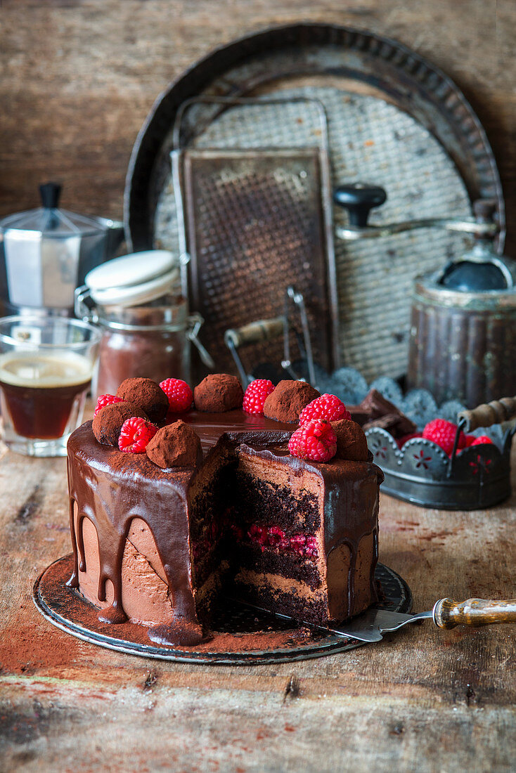 Chocolate cake with raspberry jelly and chocolate truffles, sliced