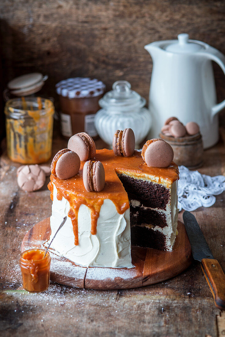 Chocolate cake with caramel and macarons, sliced