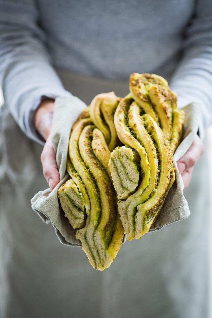 Hands holding bread plaits with wild garlic