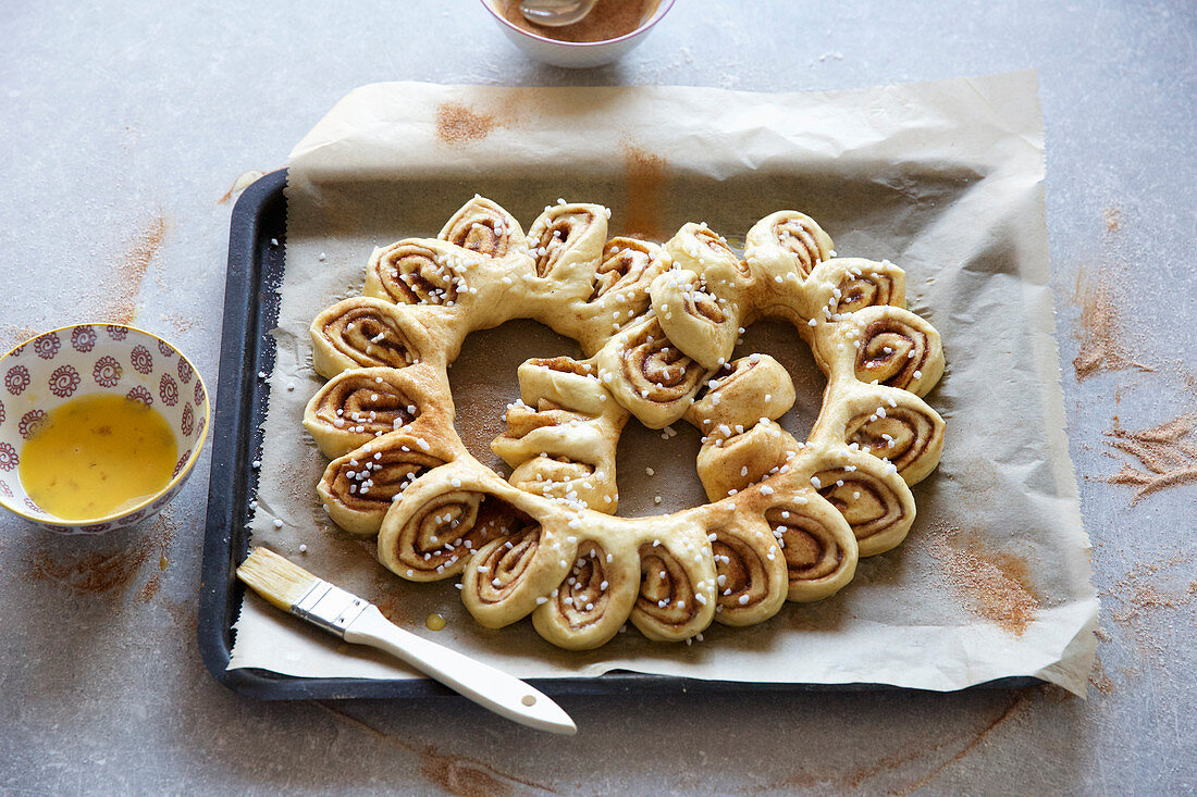 A pretzel made from cinnamon buns on a baking tray