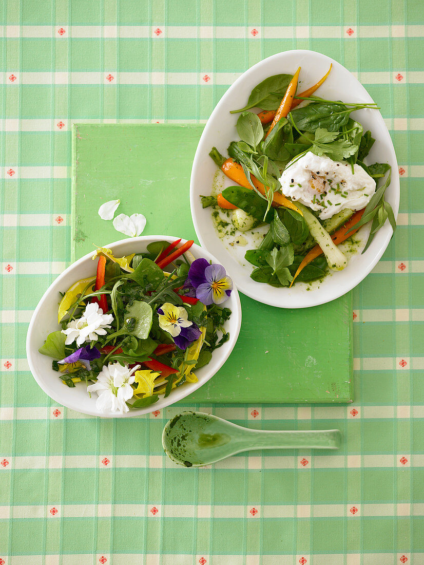 Two spring salads with edible flowers and a poached egg