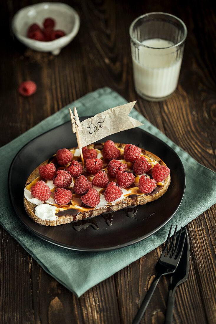 A sweet open sandwich with cream cheese, raspberries and maple syrup