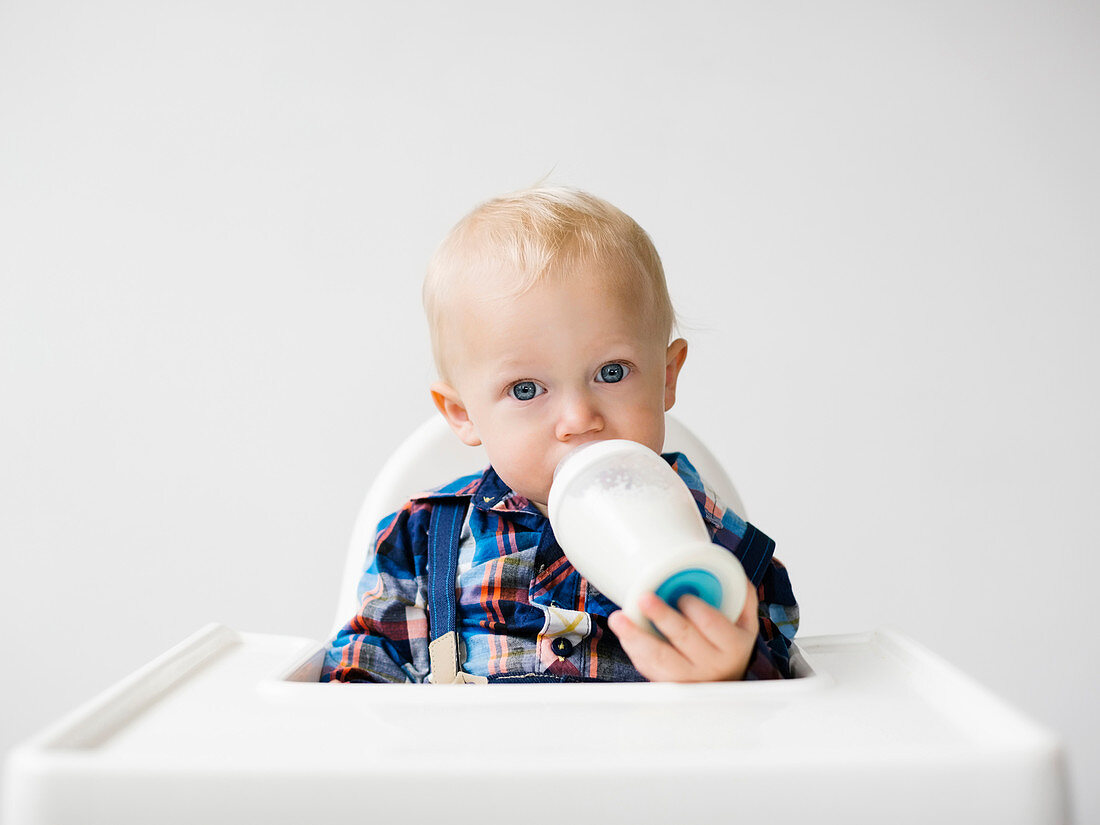 A little boy sitting in a high chair and drinking milk from a bottle