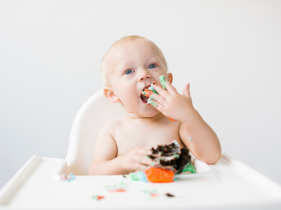 A little boy sitting in a high chair and eating a muffin for his first birthday