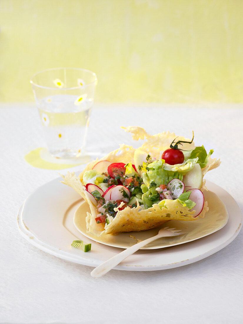 A Spring salad in a parmesan crisp with a herb vinaigrette