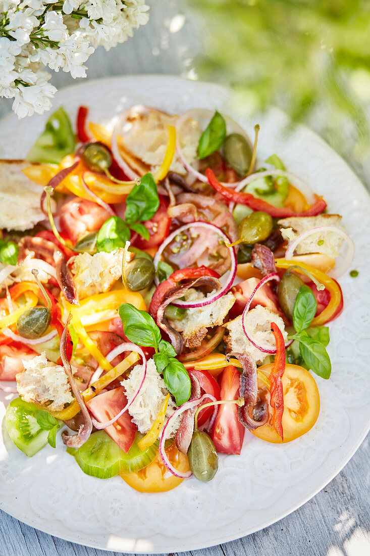 A summery tomato and bread salad on a table outdoors