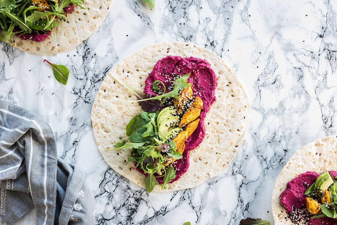 Wholegrain wraps with beetroot hummus, avocado, turmeric chicken, sesame seeds and rocket