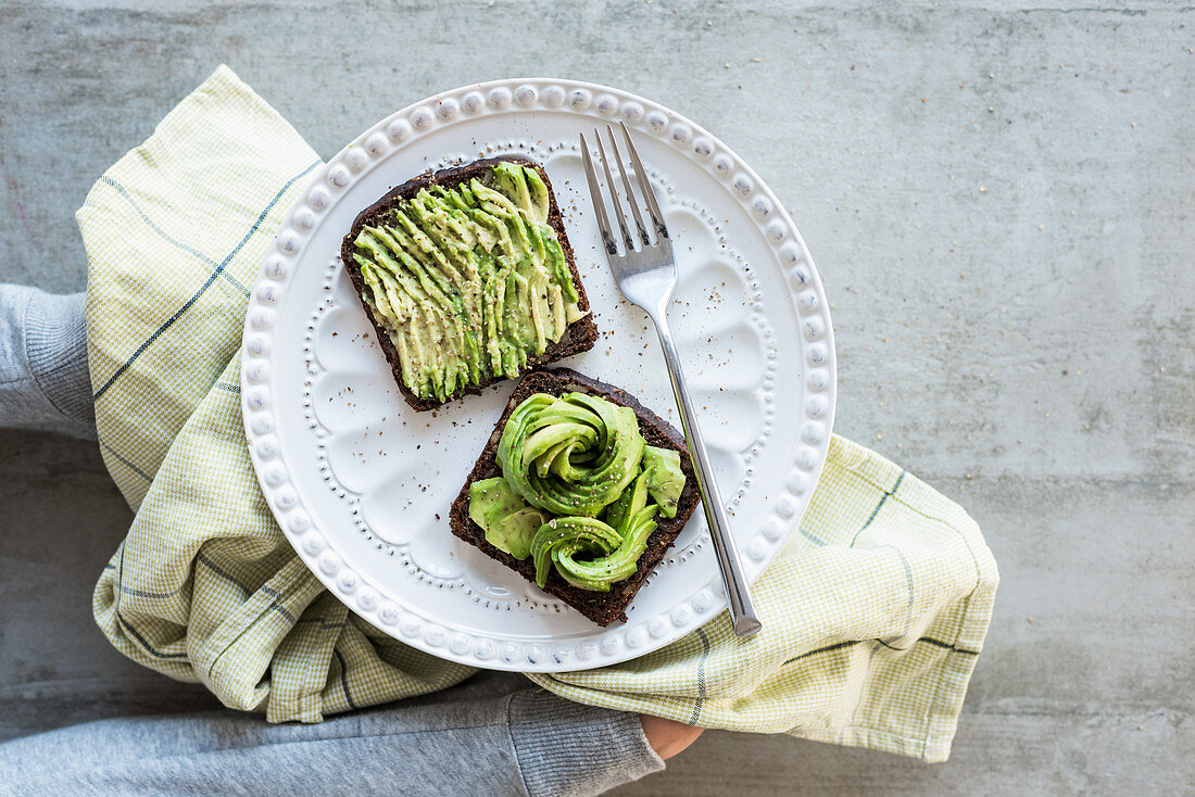 Black bread with avocado, salt and pepper
