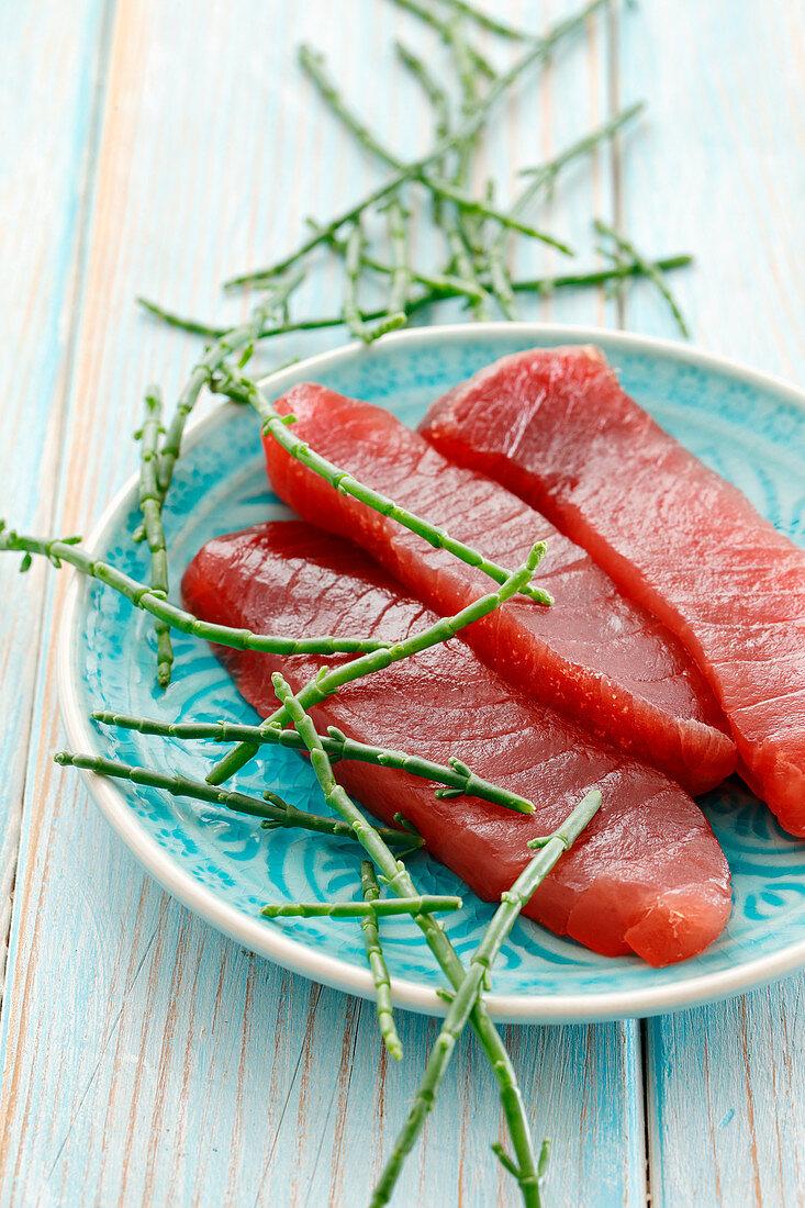 Fresh tuna fish steaks and saltwort on a plate