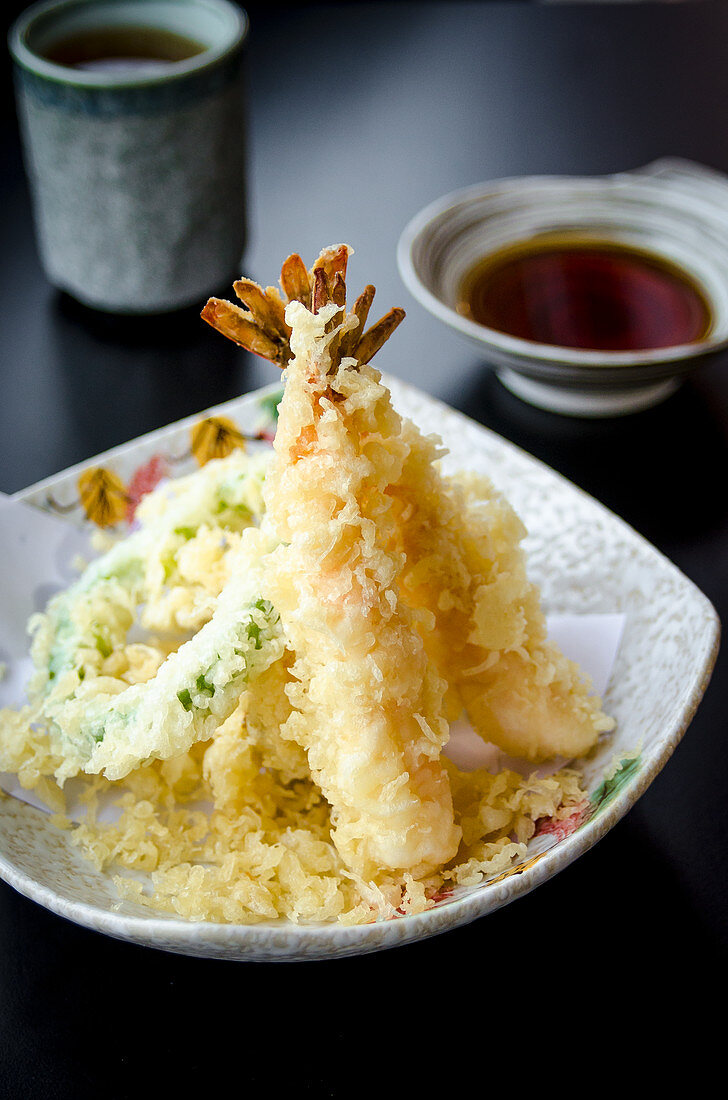 Ebi and yasay tempura with vegetables and prawns deep fried in a light tempura batter on a plate and black table served with a dashi based dipping sauce in the background and green tea