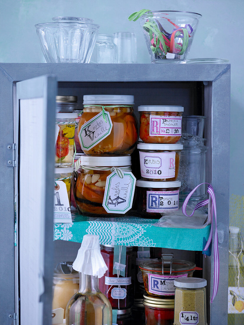 Various preserving jars in a kitchen cupboard