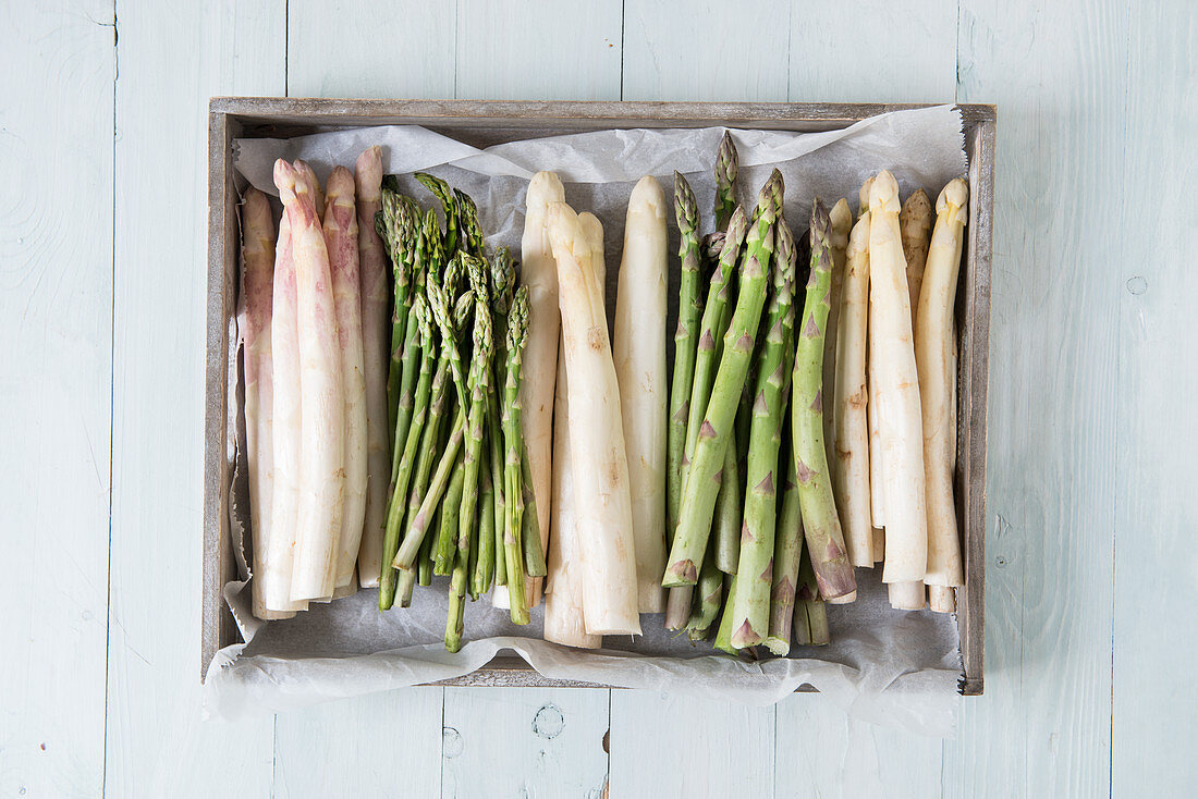 Various spears of white and green asparagus in a wooden crate