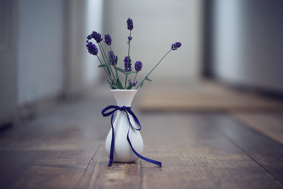 Fresh lavender flowers in a vase on a wooden floor