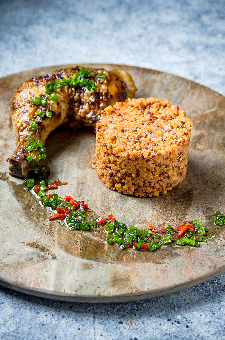 Grilled chicken drumstick and thigh with quinoa dressed with a herbs and chilli sauce on a marble plate and travertine table