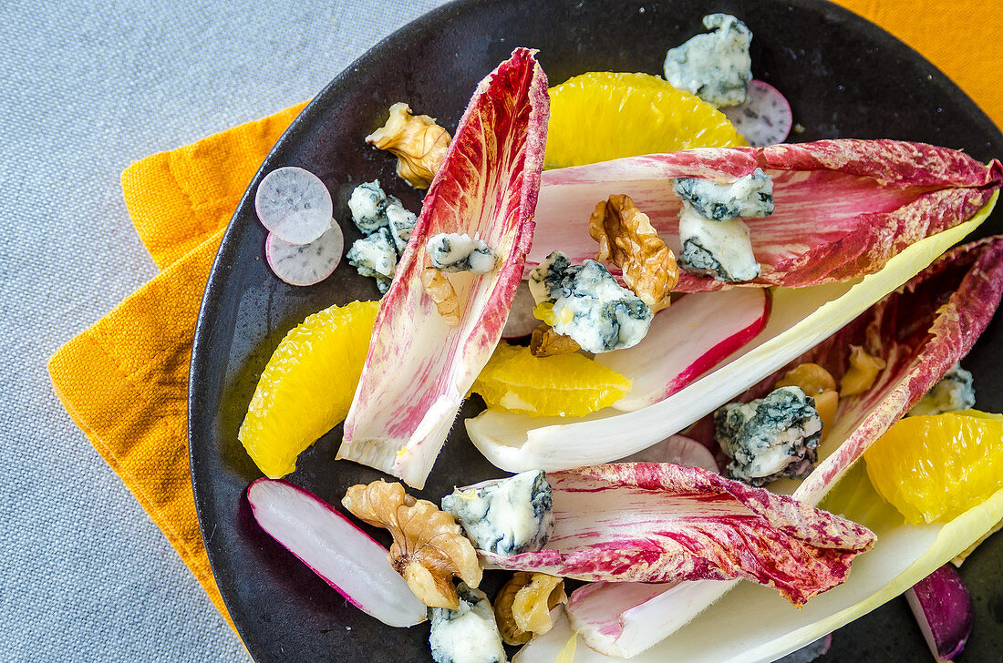 White and red chicory salad with orange, radishes, walnuts and blue cheese on a dark plate, orange napkin and light tablecloth