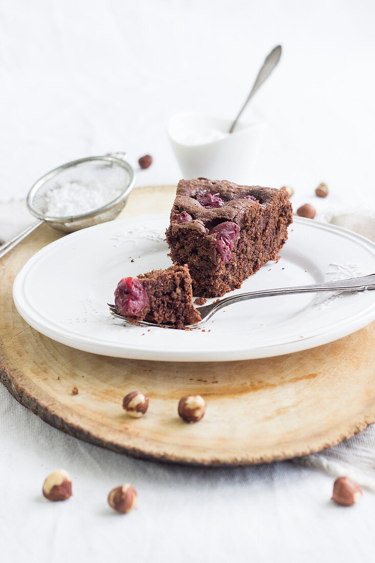 A slice of quick chocolate cherry cake with hazelnuts