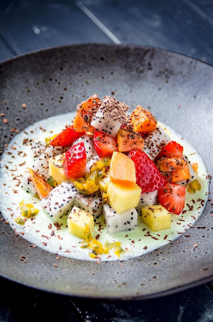 Fresh fruit salad strawberry, pinapple, dragonfruit, mango, melon, passion fruit in a green mint and yogurt dressing and chocolate shavings