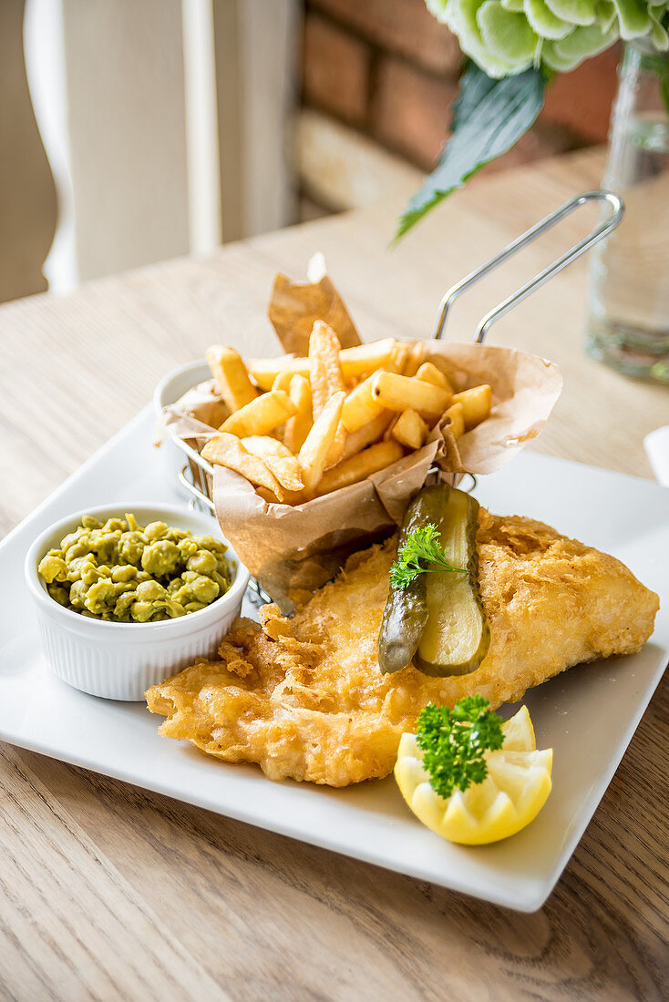 Gourmet fish and chips deep fried cod fillet in a beer batter with chips in a basket, gherkins pickle, mushy peas and half a lemon
