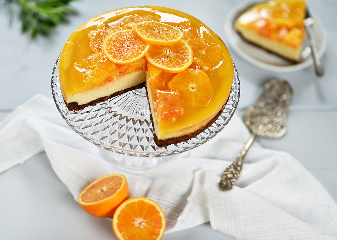 Blood orange cheesecake with a chocolate base, topped with orange slices and orange jelly (vegan)