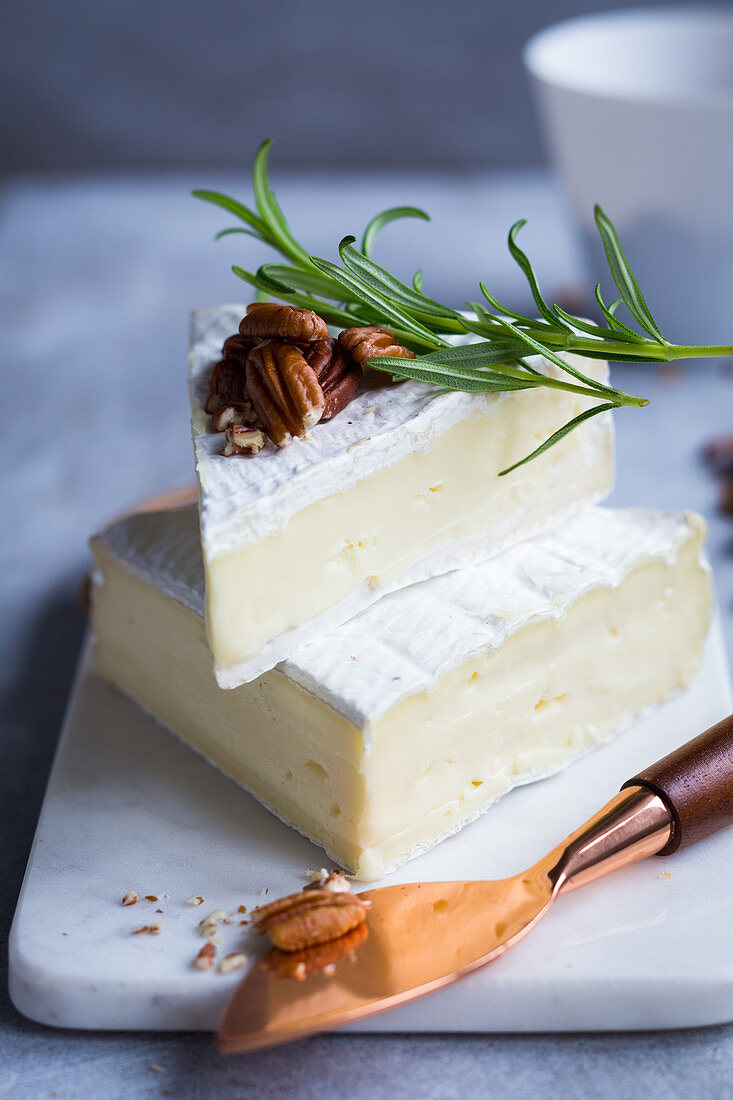 Two pieces of brie with nuts and rosemary