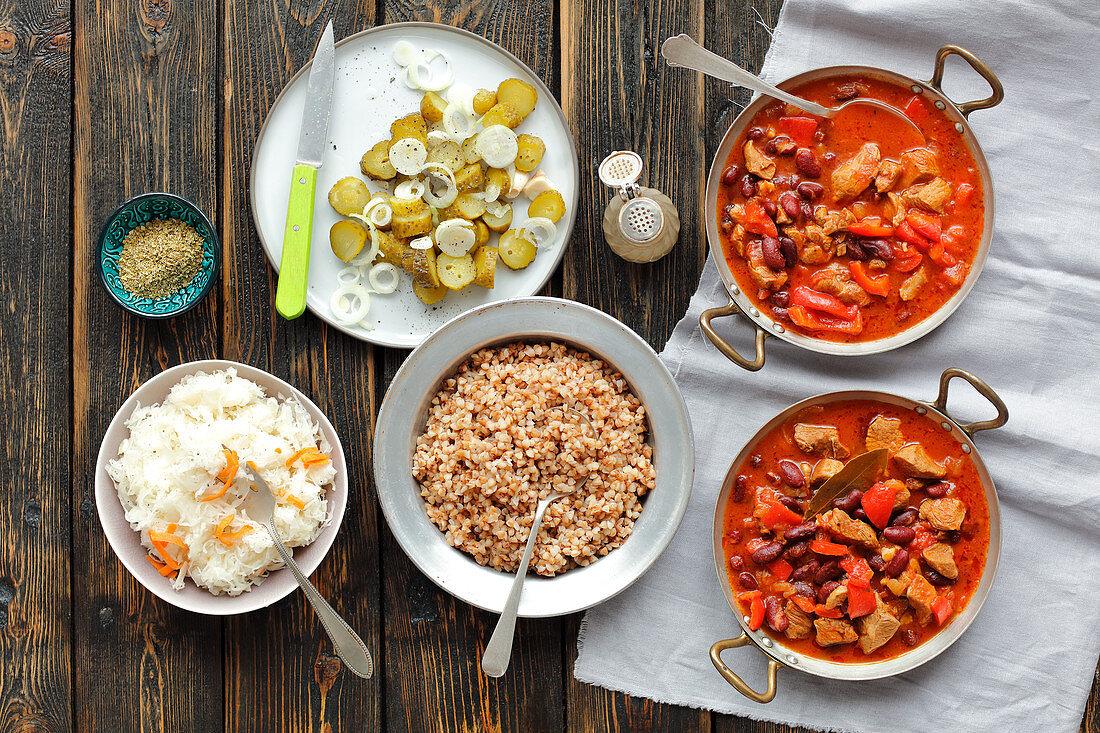Schweinegulasch mit Paprika und Kidneybohnen, dazu Buchweizen, Sauerkraut und Essiggurken