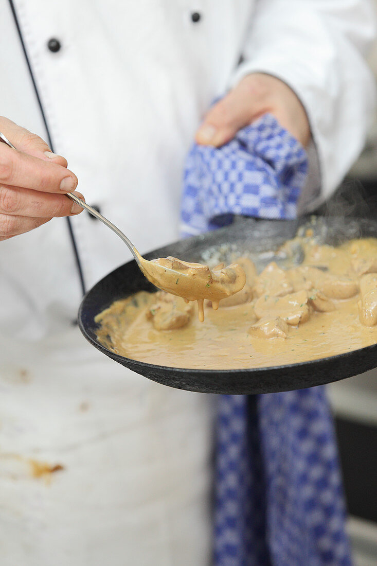 A chef holding a pan of veal kidneys in mustard and tarragon sauce