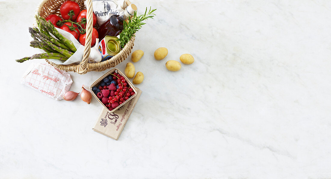 Fresh fruit, vegetables, herbs, and vinegar in a shopping basket