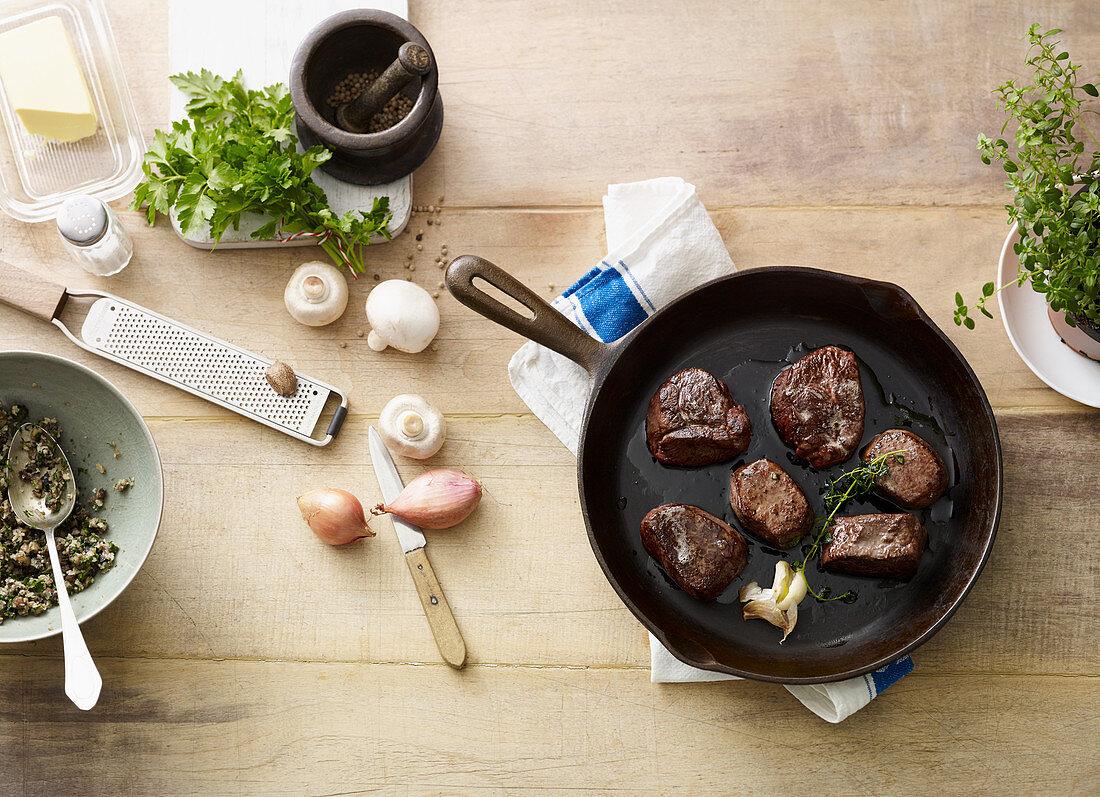 Hirschmedaillons in Pfanne mit Zutaten für Pilzkruste