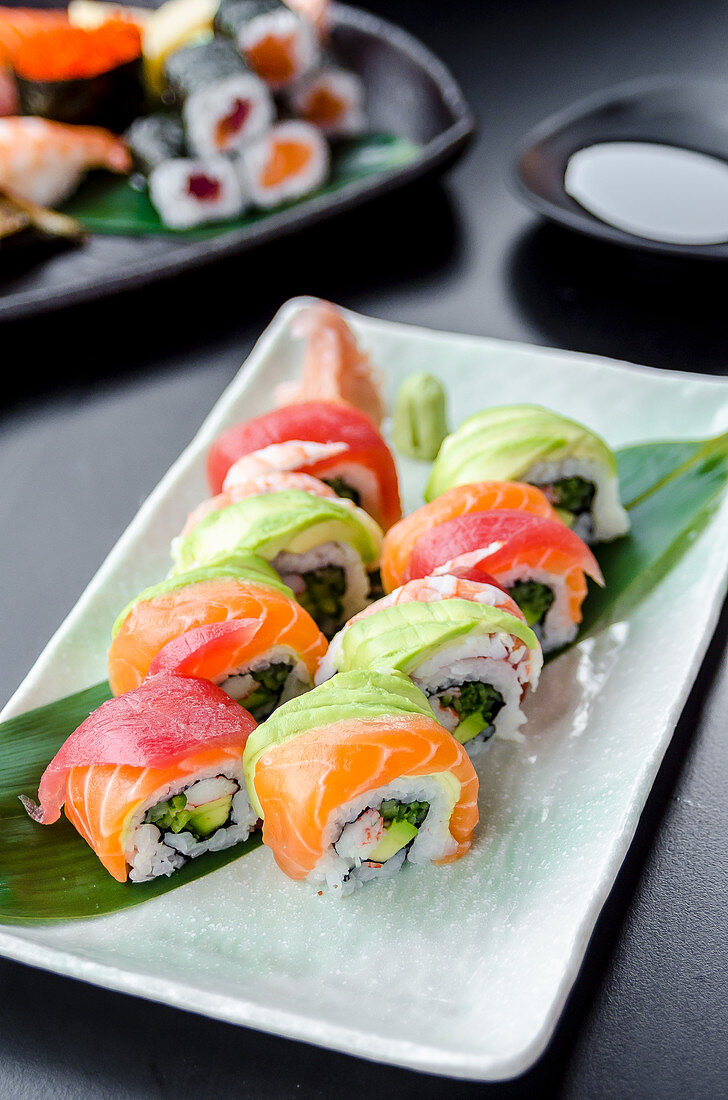 Japanese platter of rainbow rolls maki, inside out seaweed and rice roll filled with cucumber, mayonnaise, avocado, crub stick topped with fresh salmon, tuna, avocado and prawn
