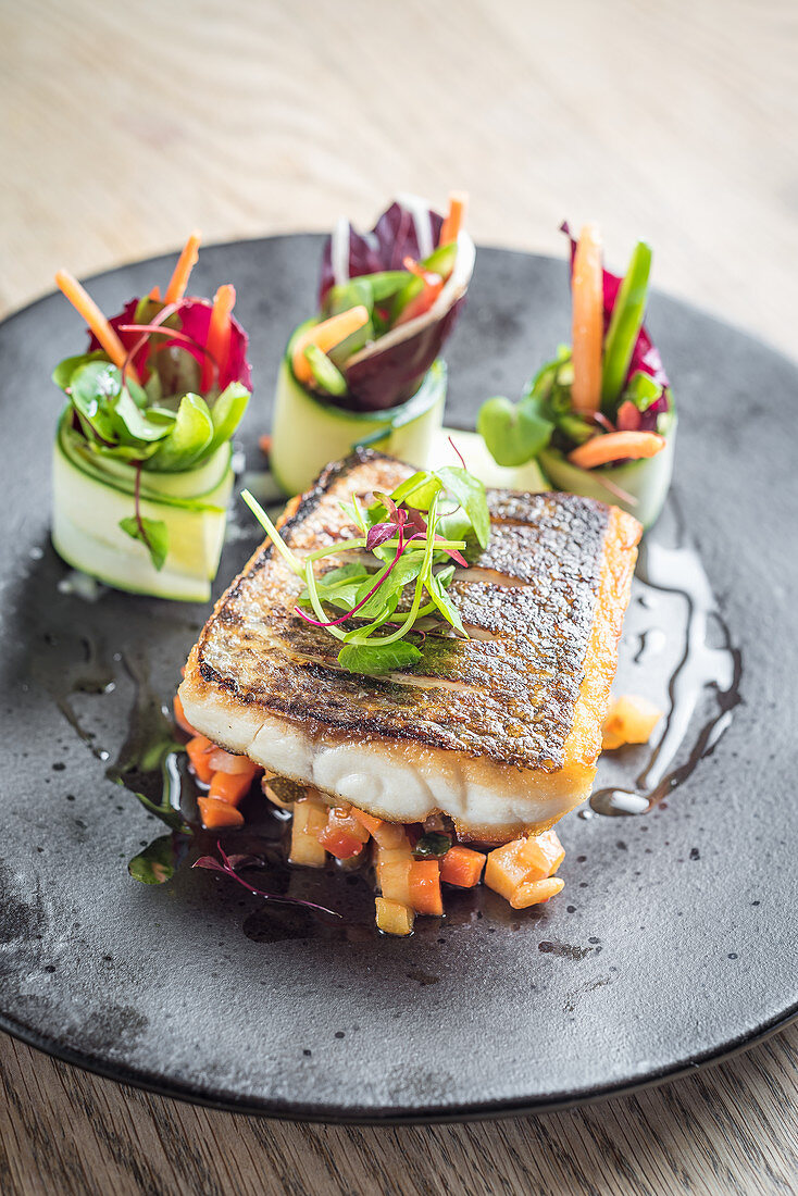 Pan fried sea bass fish fillet on a bed of diced sauteed vegetables and pretty vegetable rolls